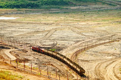 The open-pit mine, mining train carrying excavated materials at the forefront Royalty Free Stock Image
