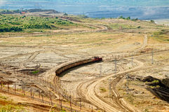 Open-pit mine, mining train carrying excavated materials. Mining machines in the background. Stock Photography
