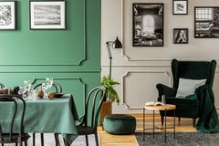 Open plan living and dining room interior with table with chairs and emerald green armchair. Open plan living and dining room interior with table with chairs and royalty free stock photos