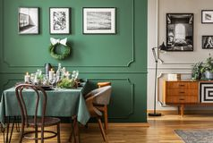 Open plan living and dining room interior with table with chairs and emerald green armchair. Open plan living and dining room interior with table with chairs and stock photos