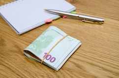 Open daily planner with ball pen, one hundred euro banknotes. On wooden table background Stock Image