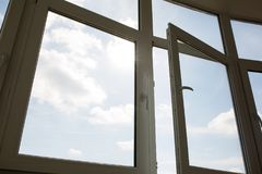 Open plastic window at the background of blue sky. Open plastic vinyl window at the background of blue sky royalty free stock photography