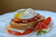 Open poached egg and sandwich with meat, bread, feta cheese, tomato on brown background. Close up Stock Images