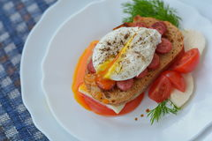 Open poached egg, sausage, tomato, feta cheese, dill, bread - fast snack. Open poached egg, sausage, tomato, feta cheese, dill, bread on white plate - fast snack Royalty Free Stock Photos