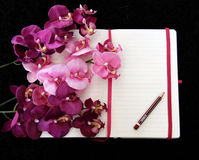 Open pocketbook with empty page and pink orchid. Royalty Free Stock Photo