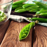 Open the pod green peas on wooden background Royalty Free Stock Image