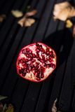 Open pomegranate on a wooden background Stock Photography