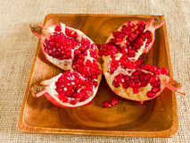 Open pomegranate on wooden plate Stock Images