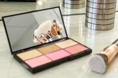 Open powder box with beige powder and pink blush, professional brush royalty free stock photo