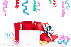 Open present with blank card. Colorful streamers over open present with blank greeting card and label; isolated on white background stock image
