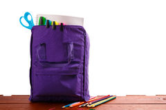 Open purple backpack with school supplies on wooden table. Back to . Close up. Stock Photos