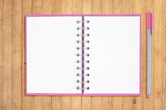 Open purple notebook and pen on wood table for background Stock Photos