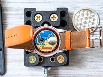 Open quartz wristwatch for replacing battery. Watch repairer workshop - open quartz wristwatch fixed in holder for replacing battery on wooden table royalty free stock photography