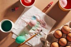 Open que empacota com ovos da galinha, pinturas novas da aquarela, escovas no papel de empacotamento Ajustado para a punição de e fotografia de stock