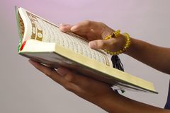 The open Qur& x27;an is held by the hand holding the prayer beads & x28;tasbih& x29;. The Qur& x27;an is the holy book of Islam. Koran arabic islamic religion royalty free stock photography