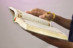 The open Qur& x27;an is held by the hand holding the prayer beads & x28;tasbih& x29;. The Qur& x27;an is the holy book of Islam. Koran arabic islamic religion royalty free stock photos