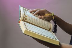 The open Qur& x27;an is held by the hand holding the prayer beads & x28;tasbih& x29;. The Qur& x27;an is the holy book of Islam. Koran arabic islamic religion stock photo
