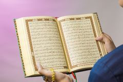 The open Quran is held by the hand holding the prayer beads. The Quran is the holy book of Islam. Koran arabic islamic religion god quran ramadan reading stock photography