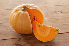 Open raw pumpkin on wooden table Royalty Free Stock Photos