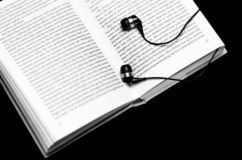 Open ready for reading the book lies on a black background close to black headphones royalty free stock photography