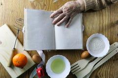 Open receptenboek in de handen van een bejaarde Stock Afbeelding