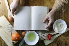 Open receptenboek in de handen van een bejaarde Stock Afbeeldingen