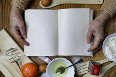 Open receptenboek in de handen van een bejaarde Royalty-vrije Stock Afbeeldingen
