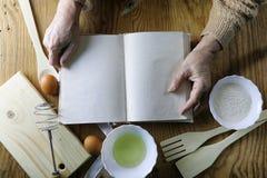 Open receptenboek in de handen van een bejaarde Royalty-vrije Stock Foto
