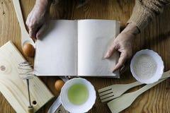 Open receptenboek in de handen van een bejaarde Stock Foto