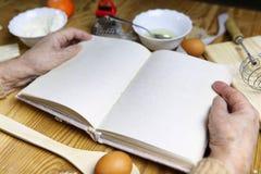 Open receptenboek in de handen van een bejaarde Royalty-vrije Stock Foto's