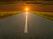 Open, rechte asfaltweg bij zonsondergang Stock Fotografie