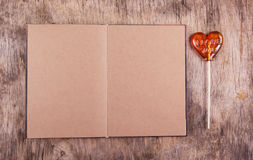 Open recipe book with blank pages and a lollipop in the shape of a heart. Open diary. Stock Photo