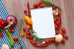 Open recipe book with fresh vegetables and herbs on wooden. Stock Image