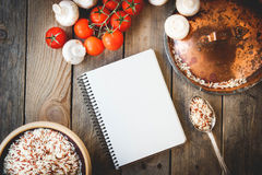 Open recipe book with fresh vegetables on wooden background Stock Images