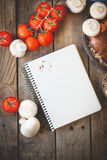 Open recipe book with fresh vegetables on wooden background Stock Photos