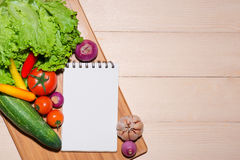 Open recipe book with fresh vegetables on wooden table. Royalty Free Stock Images