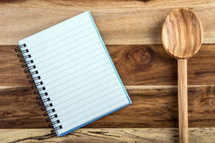 Open recipe book - notebook and wooden spoon on wooden background Royalty Free Stock Photography
