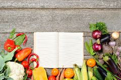 Open recipe book with set of raw organic vegetables on vintage wooden table Stock Photos