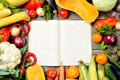 Open recipe book with set of raw organic vegetables on vintage wooden table Royalty Free Stock Image