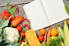 Open recipe book with set of raw organic vegetables on vintage wooden table Royalty Free Stock Images