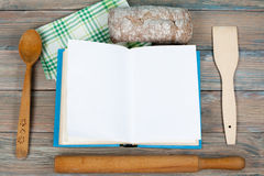 Open recipe book on wooden background, spoon, rolling pin , green checkered tablecloth. Royalty Free Stock Photo