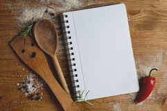 Open recipe book with wooden spoon, spatula and spices Stock Photos