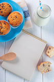 Open recipe notebook near cakes and milk in bottle Royalty Free Stock Photos