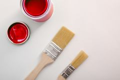 Open red acrylic paint canister on white table and paintbrushes. Conceptual background of painting material with space for text. Horizontal composition. Top royalty free stock images