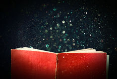Open red book and glowing glittering lights Stock Photography