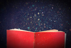 Open red book and glowing glittering lights. Stock Photo