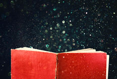 Open red book and glowing glittering lights. Royalty Free Stock Photo