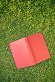 Open Red Book on Green Grass Stock Photography