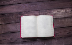 Open red book on wooden desk with soace for text.  Royalty Free Stock Image