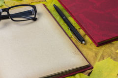 Open red book, yellow autumn foliage. Open red book and pen, autumn yellow foliage Royalty Free Stock Image